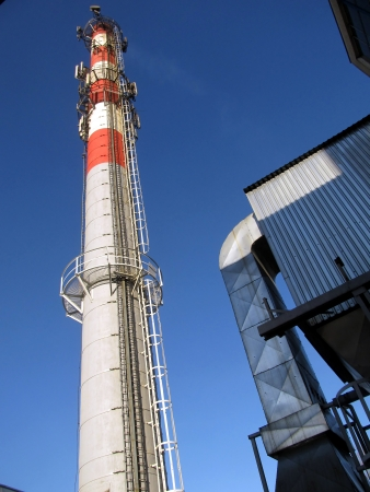 tall chimney: tall industrial chimney concrete painted white with red top Stock Photo