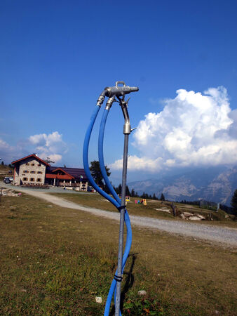 ski slope before winter in anticipation of snow, snowmaking nozzle closed, Pradalago in the Brenta Dolomites in Italy
