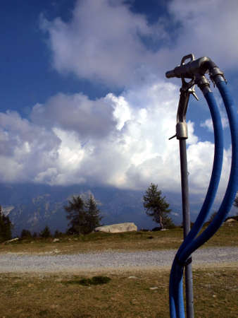 ski slope before winter in anticipation of snow, snowmaking nozzle closed, Pradalago in the Brenta Dolomites in Italy photo
