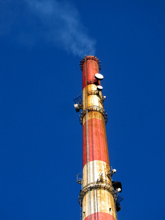 tall chimney: a tall chimney with smoke visible against the blue sky  Stock Photo