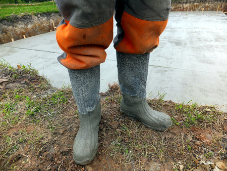 Rubber boots soiled cement during concreting photo