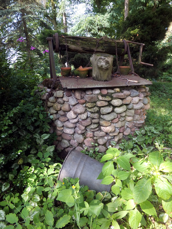 very old well built of stones overgrown with weeds, rotting winch photo