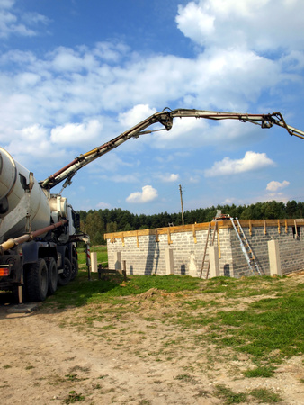 aggregates: concrete mixer truck with pump on the site is preparing to pour concrete on the roof of a small house Stock Photo