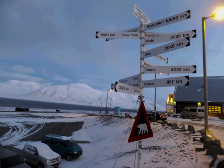 Pole with directional plaques near the Svalbard Longyear airport farthest north of the airport in the Arctic with the apparent distance to the North Pole Stock Photo