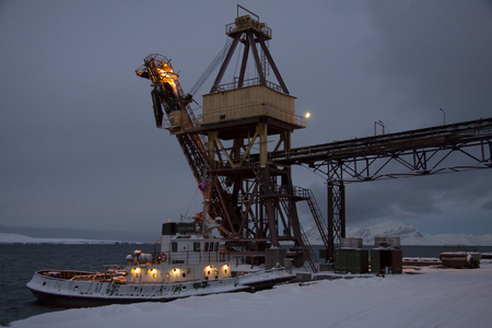 polar station: Arctic port in the Russian settlement of Barentsburg on Spitsbergen in the initial period of the polar night, a small ship in the port Editorial