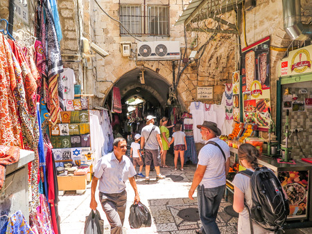 traditional goods: JERUSALEM, ISRAEL - JULY 13, 2015: Narrow stone street among stalls with traditional souvenirs and goods at bazaar in Old City - popular place among tourists and pilgrims visiting Jerusalem.