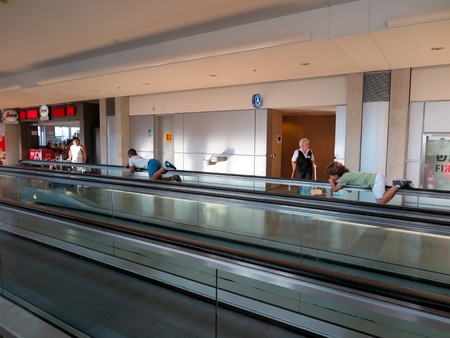antics: TELAWIW Israel - July 16, 2015: Children riding on the handrail of the escalator airport