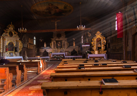 cin: KOSZECIN, POLAND 01 November 2015 .: rays of the sun illuminate the old, dark wooden church of the Holy Trinity in Koszecin, Poland Editorial