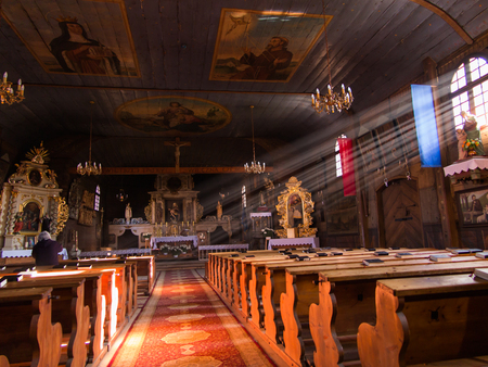 hassock: KOSZECIN, POLAND 01 November 2015 .: rays of the sun illuminate the old, dark wooden church of the Holy Trinity in Koszecin, Poland Editorial
