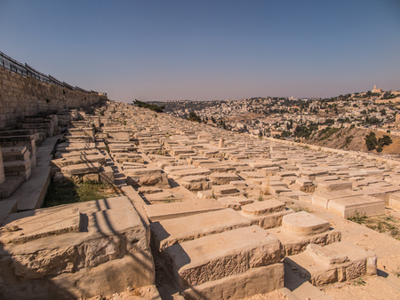 mount of olives: JERUSALEM, ISRAEL - July 13, 2015: Old jewish graves on the mount of olives in Jerusalem, with on the back the temple mount with the dome of the rock Stock Photo