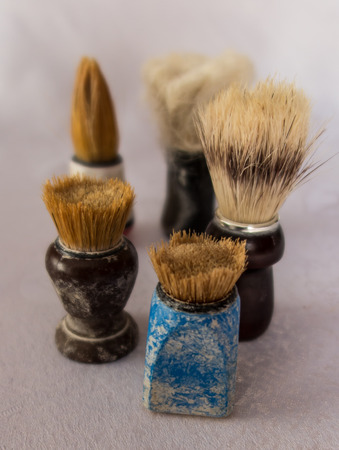 varying: new and old shaving brush in varying degrees of wear