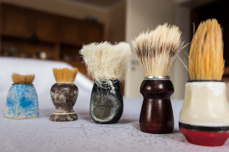 transience: new and old shaving brush in varying degrees of wear