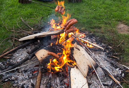 heated sausage and roasted in the flame of the fire at a picnic