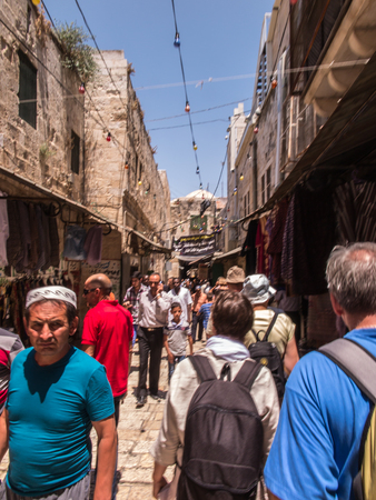 play popular: Jerusalem, Israel - July 15, 2015:  Narrow stone street among stalls with traditional souvenirs and goods at bazaar in Old City and children at play - popular place among tourists and pilgrims visiting Jerusalem.