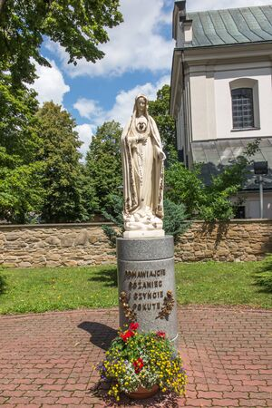 Dukla, Poland - July 20, 2016:  Figure inviting Mary to pray the rosary in front of the parish church in Dukla, Poland