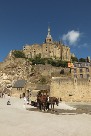 mont saint michel: Mont Saint Michel, France - September 8, 2016: Panoramic view of famous Le Mont Saint-Michel tidal island on a sunny day with blue sky and clouds, Normandy, northern France