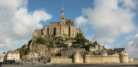 Panoramic view of famous Le Mont Saint-Michel tidal island on a sunny day with blue sky and clouds, Normandy, northern France Editorial