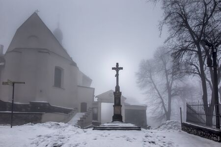 Old cross in front of the entrance to the International Shrine of St. Anna, the winter fog. Mount St. Anna, Stock Photo
