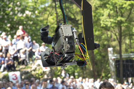 Piekary Sl, Poland, May 28, 2017: A TV camera on a jib over a crowd of men gathered at a mens clinic in Piekary Slaskie in Poland