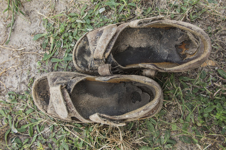 sandals old, worn out being based he and sandy earth covered with grass