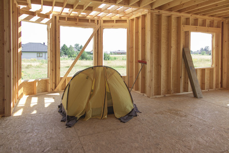 yellow tent pitched inside the built house being still without the roof Zdjęcie Seryjne