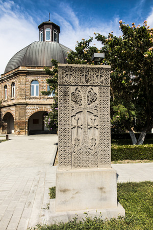 Building of the Gevorgyan Spiritual Academy with the ancient khachkar in the park in Etchmiadzin Stock Photo