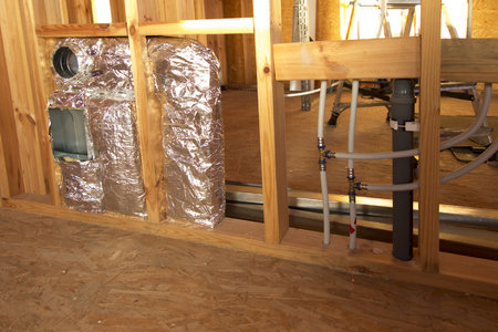 ventilation, sewage and water installation in the partition wall of a frame house Stock Photo