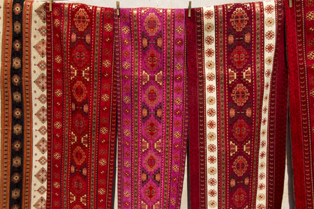colorful fabrics and other folk products at a roadside stall with traditional Armenian colors and patterns as a background