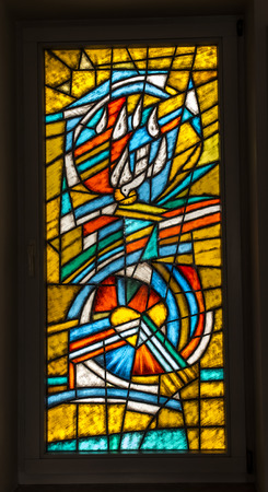 Olsztyn near Czestochowa, Poland, 25 February 2018: Colorful stained glass window with the Holy Spirit and the heart in the window of the chapel in the St. Anthonys Manor House in Olsztyn near Czestochowa in Poland