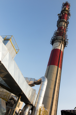 white-red industrial chimney with antennas on a background of blue sky