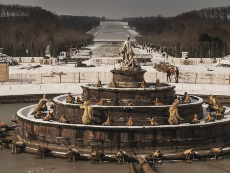 garden sculptures and pond in front of the royal residence at Versailles near Paris in France in winter scenery, the snow