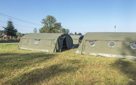 large, green, military canvas tents pitched on a meadow