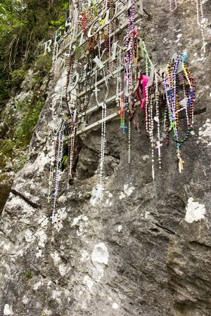 Rosaries hung on a rock at the last station of the Way of the Cross in the sanctuary of Lourdes in France.