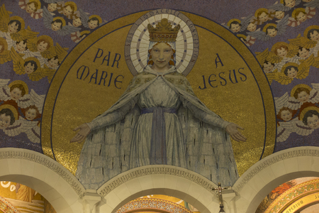 Lourdes, France, 24 June 2019: Interior of the Rosary Basilica, mosaic with the inscription