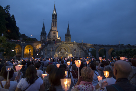 Lourdes, France, 24 June 2019: Evening procession with candles at the shrine of Lourdes in France