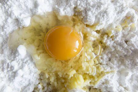 shredded potatoes, flour and broken egg on the board prepared for making dough for Silesian potato dumplings