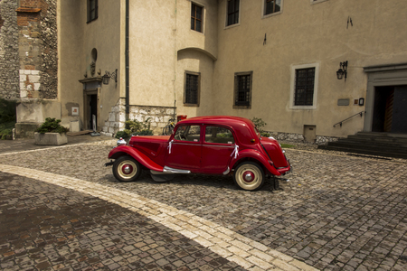 Tyniec, Krakow, Poland, August 3, 2019: Old, antique red car used to transport newlyweds at the wedding, standing in front of the church in Tyniec near Krakow in Poland. Standard-Bild - 132252343