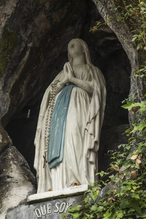 Statue of Our Lady of Immaculate Conception with a rosary in the Grotto of Massabielle in Lourdes, France