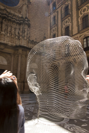 Montserrat, Spain, June 23, 2019: Head made of wire (as an object of modern architecture) in front of the entrance to the basilica at Benedictine monastery in Montserrat in Spain.