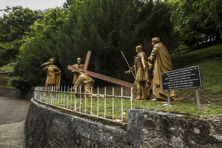 Lourdes, France, June 24 2019: Way of the Cross of Jesus, fragment of the third station - the first fall of Jesus under the cross Sajtókép