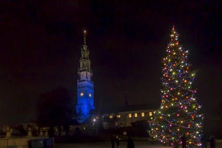 The tower in the sanctuary at Jasna Góra in Czestochowa in Poland illuminated in blue on the day of Saint Mary the Holy Mother of God in the evening on the first day New Year 2020. 写真素材