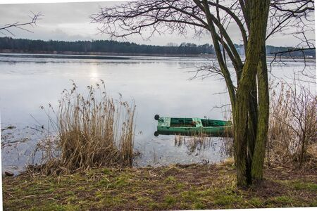 old, green, boat submerged in the water at the bank of the pond on the Mala Panew river in Kalety Zielona in Poland, in winter