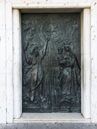 An ornate door to the Slella Maris Basilica in Haifa, Israel, depicts Elijah and Mary with Jesus and the Carmelite Scapular