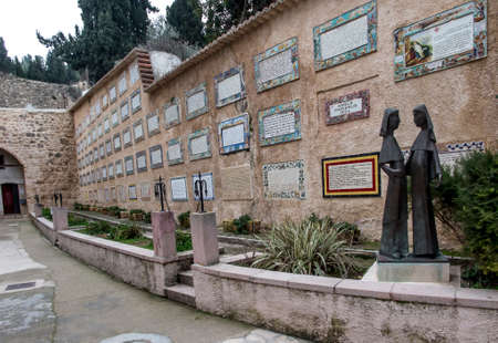Ein Karem, ISRAEL - January 28, 2020: Figures of pregnant Mary and Elizabeth related to the visitation of Elizabeth by Mary in Ein Karem. In the background plates on the wall with the text of worship