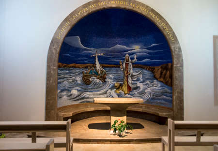 Magdala, Israel, January 26, 2020: Side altar in the church in Magdala on the Galilee Lake (Tiberiacn) with a mosaic depicting Jesus walking on the lake with the inscription: Lord, save me. Why did you doubt little faith? Banque d'images - 150899325