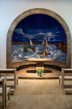 Magdala, Israel, January 26, 2020: Side altar in the church in Magdala on the Galilee Lake (Tiberiacn) with a mosaic depicting Jesus walking on the lake with the inscription: Lord, save me. Why did you doubt little faith? Banque d'images - 150899326