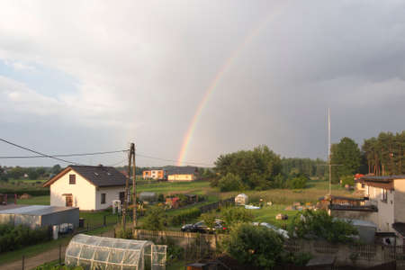 rainbow over a wooden house in a rural setting