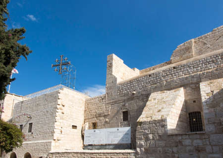 Square in front of the Basilica of the Nativity of Jesus Christ in Bethlehem, Palestine. Visible entrance. Blue sky with white clouds