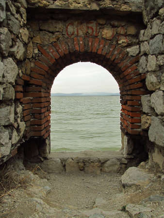 Fragment of a brick arch in a stone wall. Ruins of Golubac Castle in Serbia