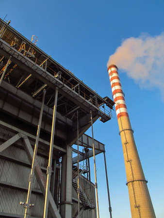a tall, white and red chimney and a fragment of the power plant building